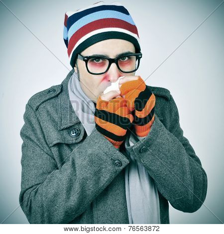 a man with a cold bundled up in a coat, knit cap, gloves and scarf