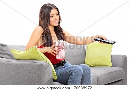 Young woman watching TV seated on a sofa and holding a box of popcorn isolated on white background