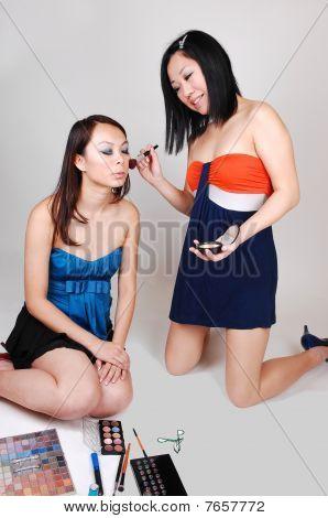 zwei chinesische Mädchen tun Make-up.