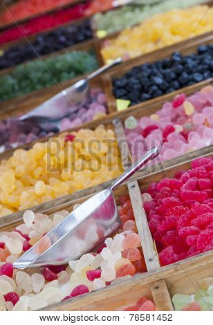 Close-up image of colorful jellies on a street market stand. Selective focus on the dipper. poster