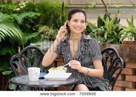 junge Frau Gespräch auf einem Handy während des Mittagessens