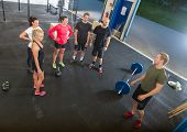 High angle view of young male trainer talking to athletes in gym poster