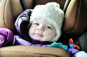 8 months old baby girl in a safety car seat with catch frame system poster
