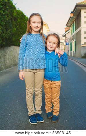 Two adorable kids in a city, girl and her little brother, wearing blue and beige clothes