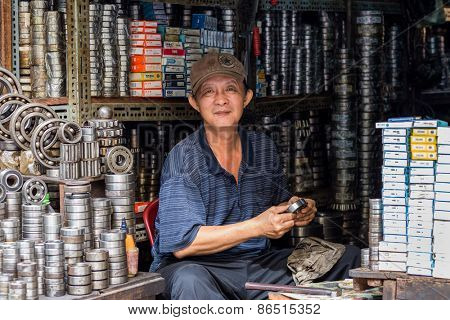 CAN THO, VIETNAM, DECEMBER 11, 2014: Portrait of A ball bearing seller cleaning a stuff in the Tan An market streets in Can Tho city, Vietnam.