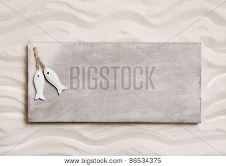 Wooden background with sand and two fishes on an sign like a message board.