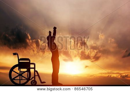 A disabled man standing up from wheelchair at sunset. Positive concept of cure, recovery, medical miracle, hope, insurance etc.  poster