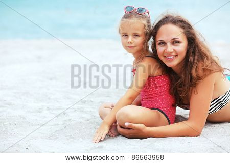 Happy family resting at beach in summer, mother with her 5 years old child