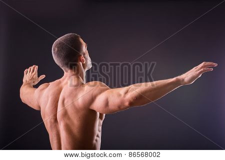 Muscular man bodybuilder. Man posing on a black background, shows his muscles. Bodybuilding, posing, black background, muscles - the concept of bodybuilding. Article about bodybuilding. poster