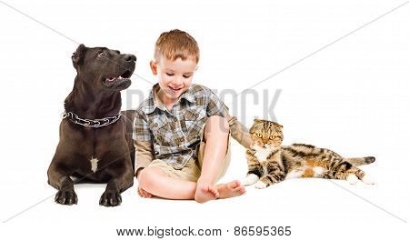 Happy boy sitting with dog and cat