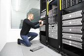 It engineer or technician maintaning storage area network SAN in data rack. Shot in datacenter. poster