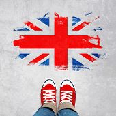 British Urban Youth Concept Feet in Red Sneakers from Above Standing in front of Grunge Great Britain Flag. poster