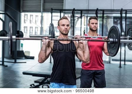Muscular men lifting a barbell at the crossfit gym