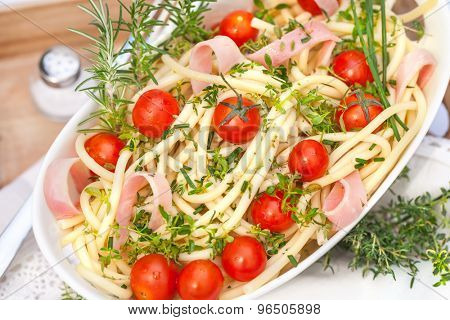 Portion of salad with noodles and herb and tomatoes