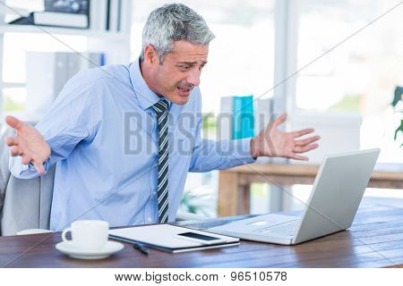 Confused businessman looking at laptop computer in office