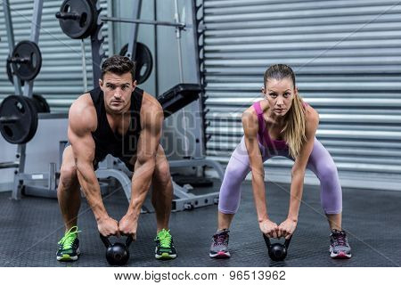 Portrait of a muscular couple lifting kettlebells at the health club poster
