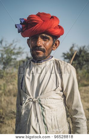 GODWAR REGION, INDIA - 13 FEBRUARY 2015: Rabari tribesman holds traditional ax on field. Post-processed with grain, texture and colour effect.