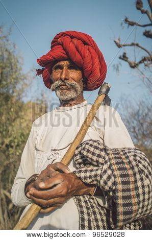 GODWAR REGION, INDIA - 13 FEBRUARY 2015: Rabari tribesman holds traditional ax on field and watches herd. Post-processed with grain, texture and colour effect.