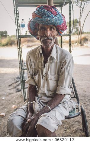 GODWAR REGION, INDIA - 13 FEBRUARY 2015: Indian tribesman sits on chair in chai shop with colorful turban on head. Post-processed with grain, texture and colour effect.