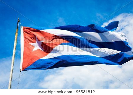 The flag of Cuba waving in the wind against a blue sky.