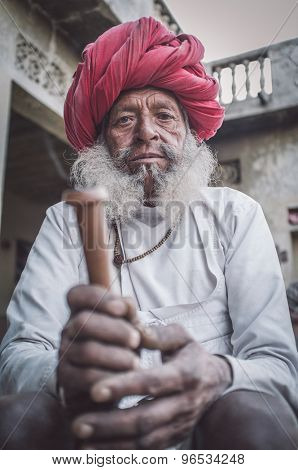 GODWAR REGION, INDIA - 12 FEBRUARY 2015: Elderly Rabari tribesman with traditional turban, clothes and long beard holds chillum. Post-processed with grain, texture and colour effect.