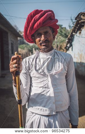 GODWAR REGION, INDIA - 13 FEBRUARY 2015: Rabari tribesman stands in courtyard of home wearing traditional clothes and holds herding stick. Post-processed with grain, texture and colour effect.
