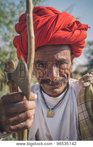 GODWAR REGION, INDIA - 14 FEBRUARY 2015: Elderly Rabari tribesman with red turban sits and holds ax and stick. Post-processed with grain, texture and colour effect.