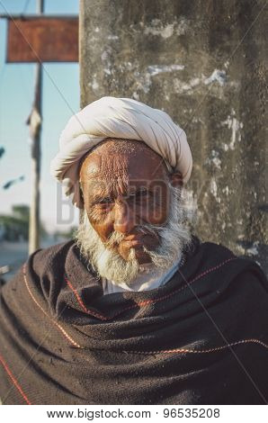GODWAR REGION, INDIA - 14 FEBRUARY 2015: Elderly tribesman with white turban and dark blanket. Post-processed with grain, texture and colour effect.