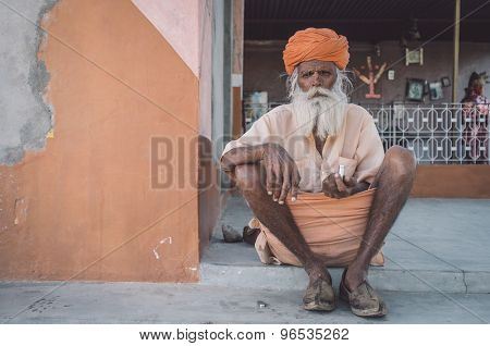 GODWAR, INDIA - 12 FEBRUARY 2015: Elderly Indian tribesman with turban in lungi sits on ground in front of temple. Post-processed with grain, texture and colour effect.