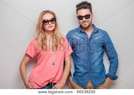 Smiling young casual couple looking at the camera while holding hands in pockets.