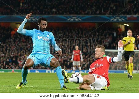 LONDON, ENGLAND - Nov 26 2013: Marseille's Nicolas N'Koulou and Arsenal's Jack Wilshere compete for the ball during the UEFA Champions League match between Arsenal and Olympique de Marseille
