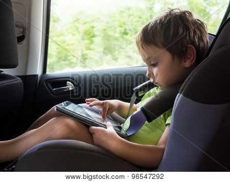 Little Boy Playing On Computer Tablet  In The Car