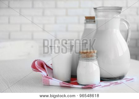 Pitcher, jars and glass of milk on wooden table, on bricks wall background