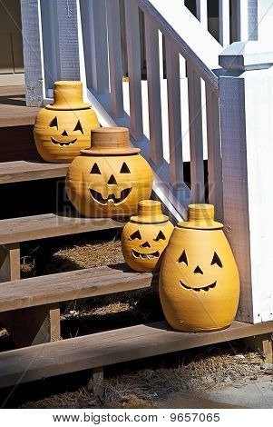 Four pumpkins lined up on the steps of a house. poster