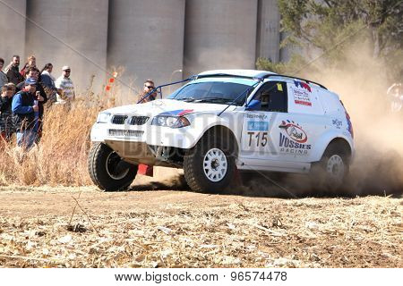 Drifting White Bmw Rally Car Kicking Up Dust On Turn.