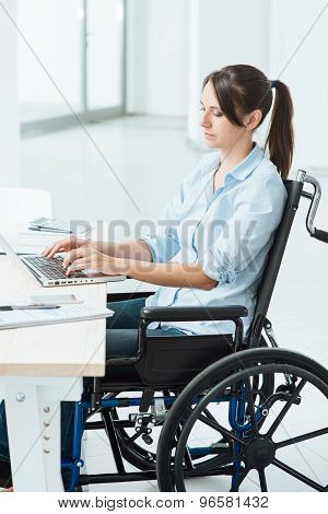 Young disabled business woman in wheelchair working at office desk and typing on a laptop accessibility and independence concept poster