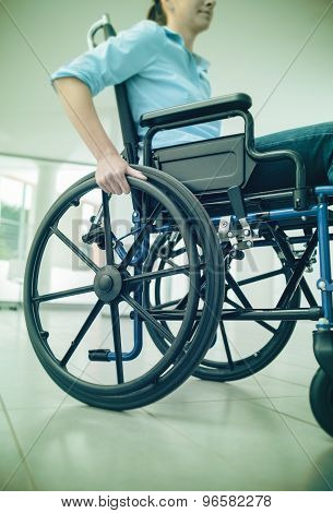 Young woman in wheelchair hand pushing on wheel close up disability and handicap concept poster