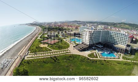 RUSSIA, ADLER - JUL 25, 2014: Sea beach near territory of hotel Radisson Blu at summer sunny day. Aerial view. Photo with noise from action camera.