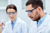 science, chemistry, technology, biology and people concept - close up of young scientists at laboratory poster