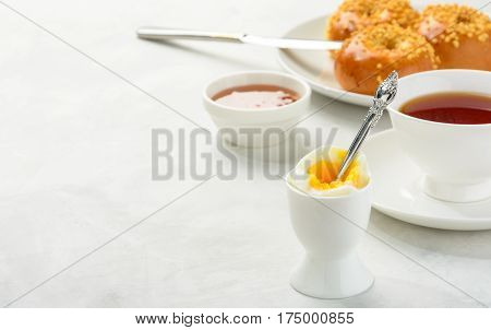 Delicious and healthy breakfast of boiled egg and brioche buns with black tea on a light background. Copy spacesoft focus.