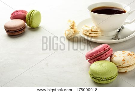 Cup of black tea with varicolored macaroons on a white background in light key. Copy space.
