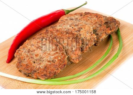 liver pancakes or cutlets with chilli and spring onions on a cutting board isolated on white background.