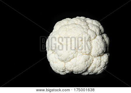 Whole raw cauliflower isolated on black background