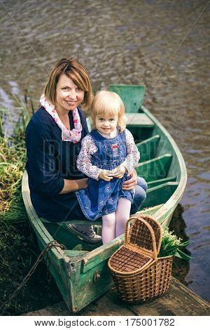 Portrait of happy family of two people on vacation. Young mother and little daughter on picnic sitting in old wooden boat on spring river over water background. Age of child 2 years and 4 month.