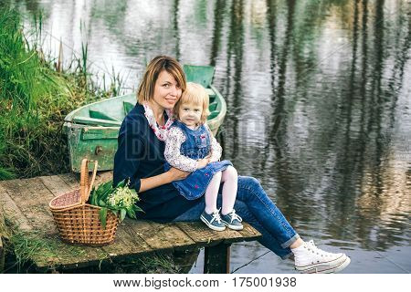 Portrait of happy family of two people on vacation. Young mother and little daughter on picnic near spring river and old wooden boat over beautiful water background. Age of child 2 years and 4 month.