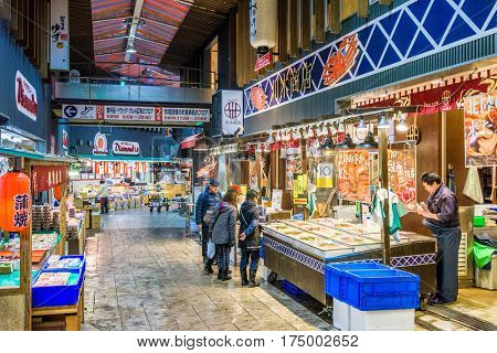 KANAZAWA, JAPAN - JANUARY 17, 2017: Early morning shoppers peruse fresh seafood at the the Omicho Market.