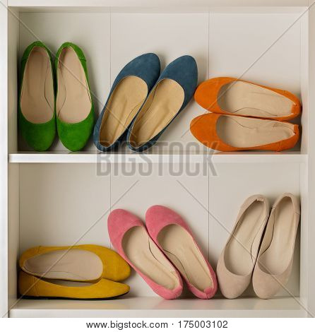 Rows of colorful women's shoes (ballet shoes) in the wardrobe. Selective focus.