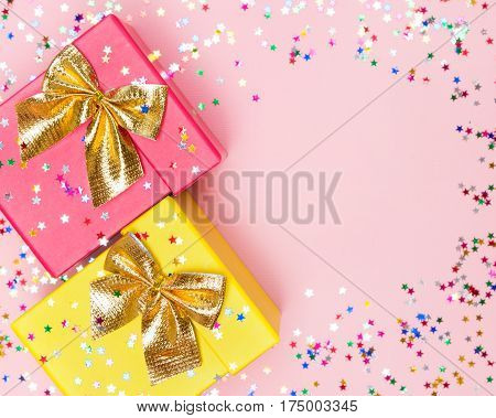 Celebratory background with two color gift boxes, golden bows and sparkling confetti