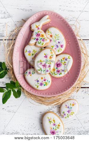Biscuits colorful Easter cookies on wooden background. Floral icing decorated cookies.