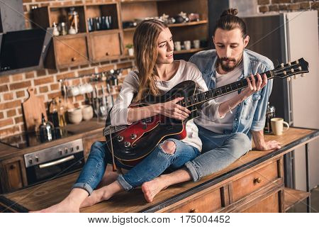 Beutiful young woman playing song on guitar for her boyfriend